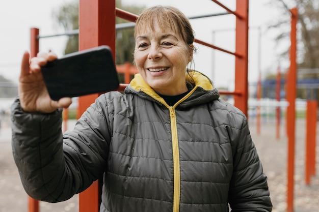 Smiley ältere frau, die ein video auf ihrem smartphone sieht