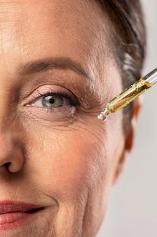 Smiley ältere frau, die serum für ihre augenfalten verwendet