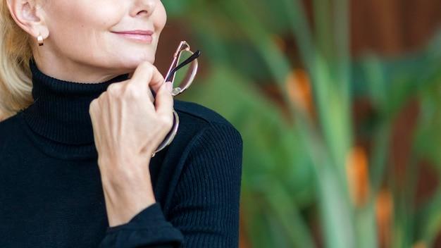 Smiley ältere frau hält brille während aus