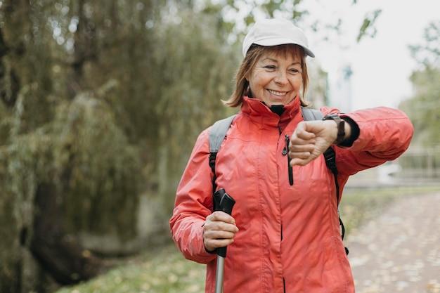 Smiley ältere frau mit trekkingstöcken im freien, die ihre uhr betrachten