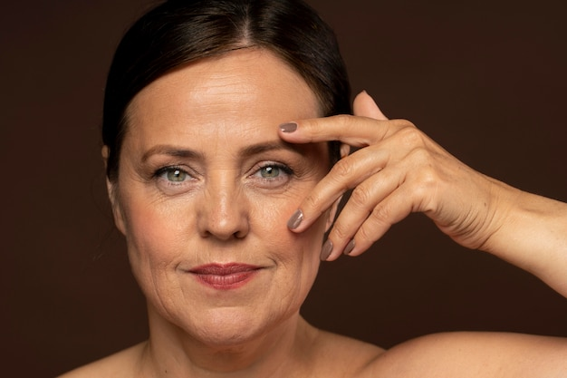 Smiley ältere frau posiert mit make-up auf und zeigt nägel