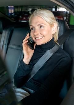 Smiley ältere geschäftsfrau auf einem telefonanruf im auto