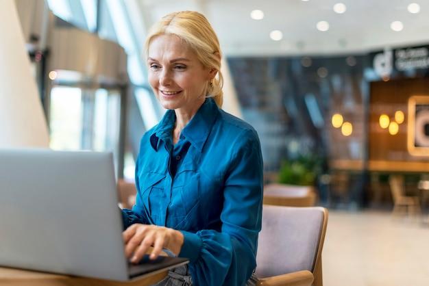 Smiley ältere geschäftsfrau, die am laptop arbeitet, während heraus