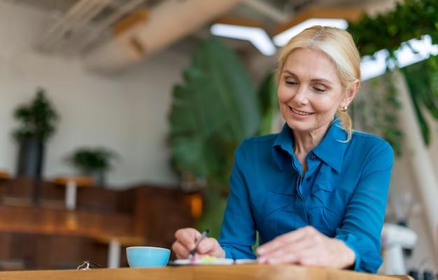 Smiley ältere geschäftsfrau, die in der tagesordnung beim abendessen schreibt