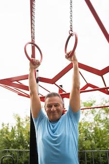 Smiley älterer mann, der draußen trainiert