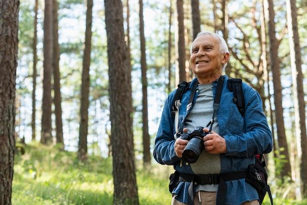 Smiley älterer mann, der natur mit kamera erforscht