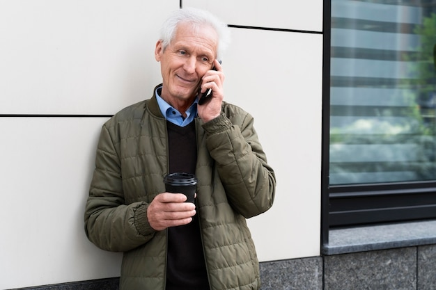 Smiley älterer mann in der stadt, der beim kaffeetrinken auf dem smartphone spricht
