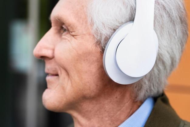 Smiley älterer mann in der stadt, der musik über kopfhörer hört