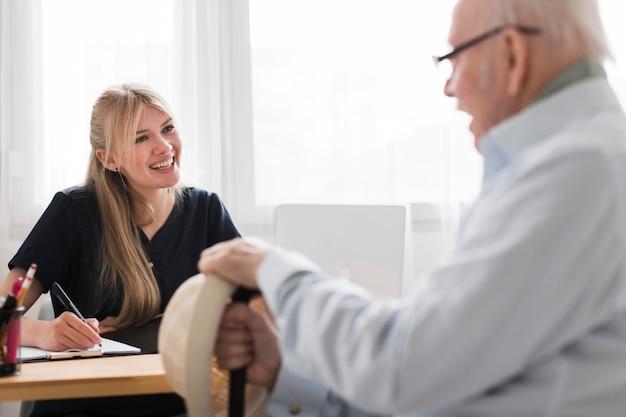 Smiley älterer mann in einem pflegeheim mit weiblicher krankenschwester