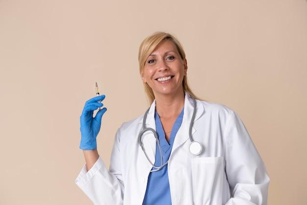 Smiley ärztin hält eine impfspritze