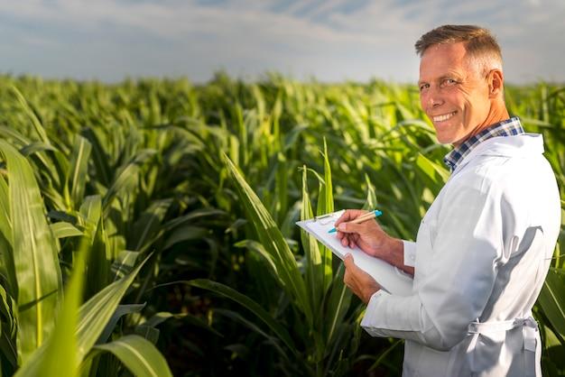 Smiley-agronom, der kamera mit einem klemmbrett betrachtet
