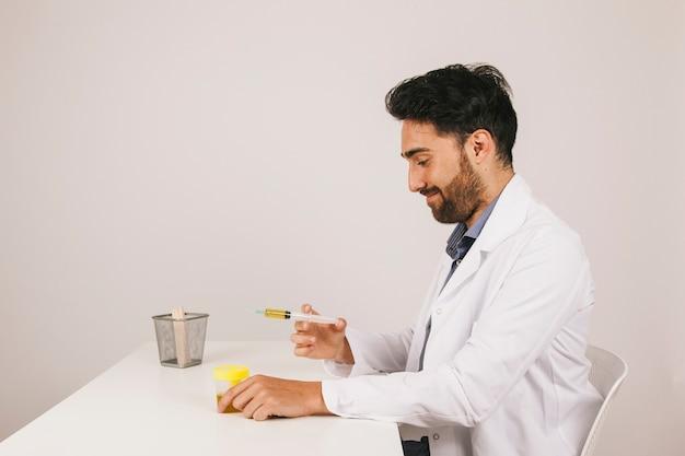 Smiley arzt arbeitet mit einem urin-test eine spritze
