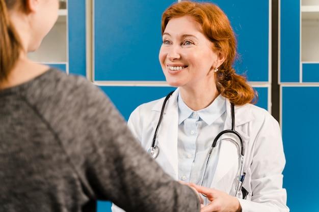 Smiley-arzt schaut patienten an