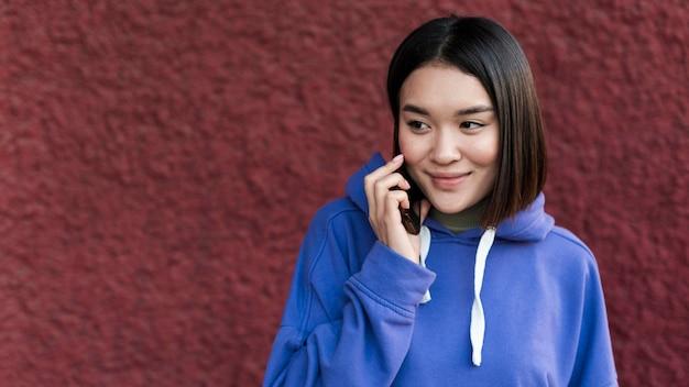 Smiley asiatische frau, die am telefon mit kopienraum spricht