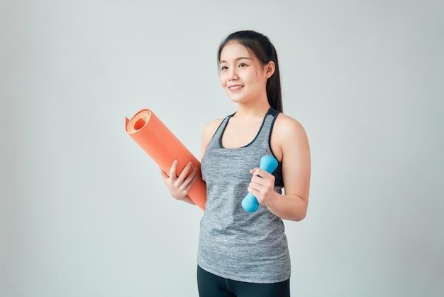 Smiley asiatische frau, die sportkleidung trägt, die orange matte mit blauer hantel im wohnzimmer hält. gesundes lebensstilkonzept.