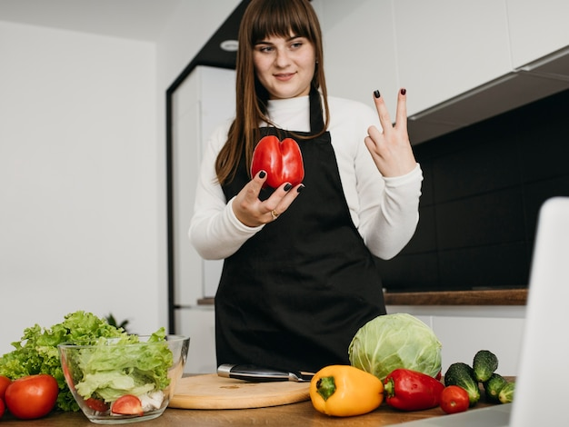 Smiley-bloggerin beim kochen mit laptop