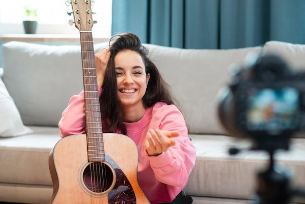 Smiley-bloggerin posiert mit ihrer gitarre