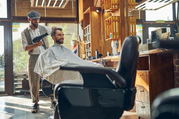 Smiley brunette kunde eines barbershops, der seinen neuen haarschnitt von einem friseur föhnen lässt