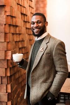 Smiley charmanter mann, der eine tasse kaffee hält