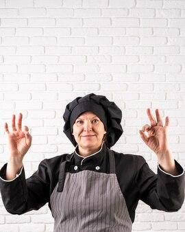 Smiley chef posiert beim ok zeichen machen