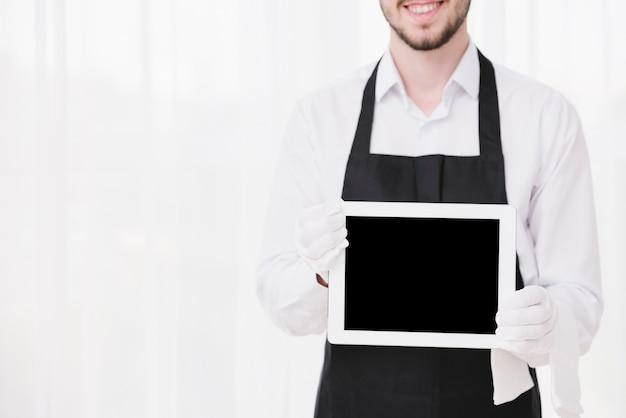 Smiley-diener, der eine tablette mit modell hält