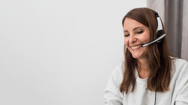 Smiley erwachsene frau, die arbeit von zu hause aus genießt
