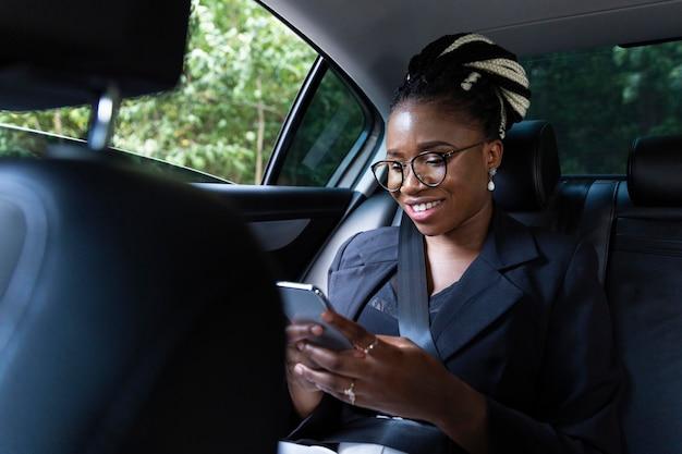 Smiley-frau auf dem rücksitz ihres autos, das tablette betrachtet