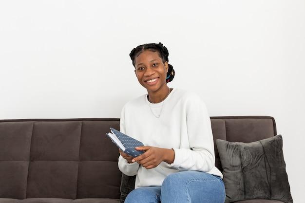 Smiley-frau auf der couch mit buch