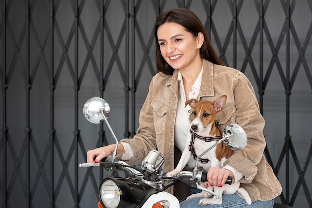 Smiley-frau auf roller mit ihrem hund