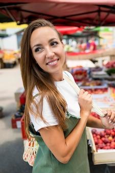 Smiley-frau beim einkaufen von lebensmitteln