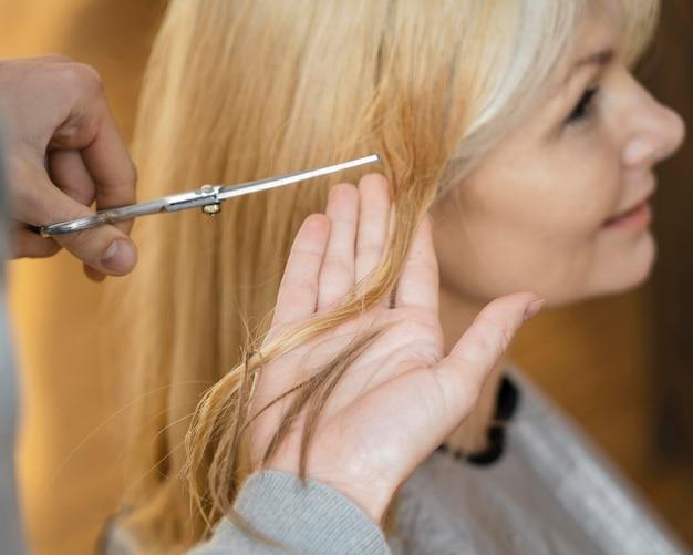 Smiley-frau bekommt einen haarschnitt zu hause mit friseur
