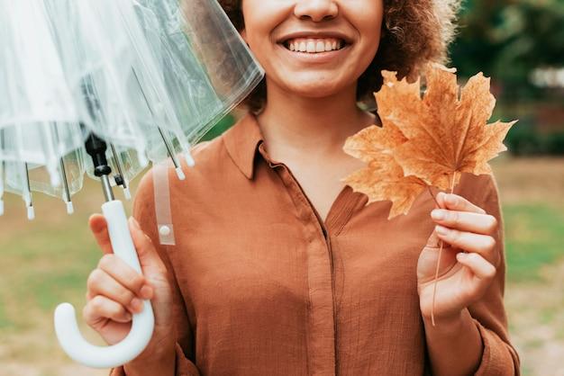 Smiley-frau der vorderansicht, die ein blatt und einen regenschirm hält