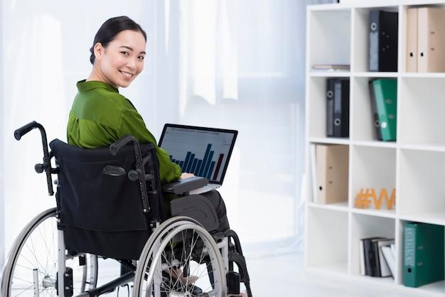 Smiley-frau, die am laptop arbeitet
