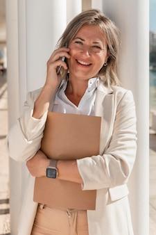 Smiley-frau, die am telefon mittlerer schuss spricht
