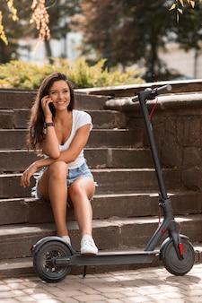 Smiley-frau, die am telefon neben elektroroller spricht