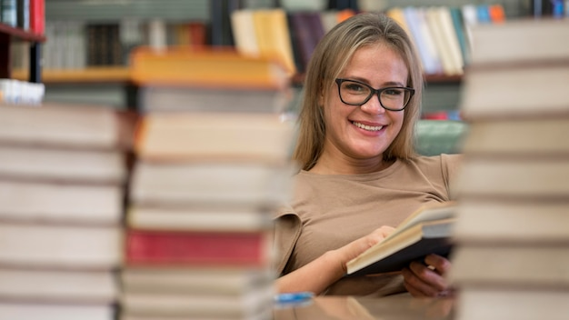 Smiley-frau, die an der bibliothek studiert