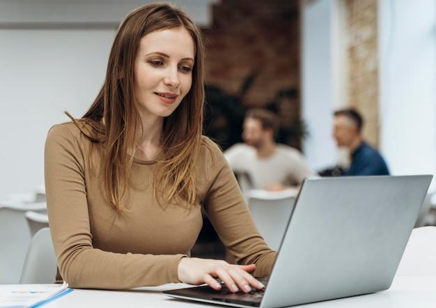 Smiley-frau, die an einem laptop arbeitet