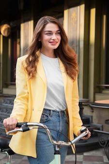 Smiley-frau, die auf der straße aufwirft, während sie ihr fahrrad hält