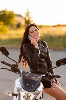 Smiley-frau, die auf smartphone spricht, während sie auf ihrem motorrad sitzt
