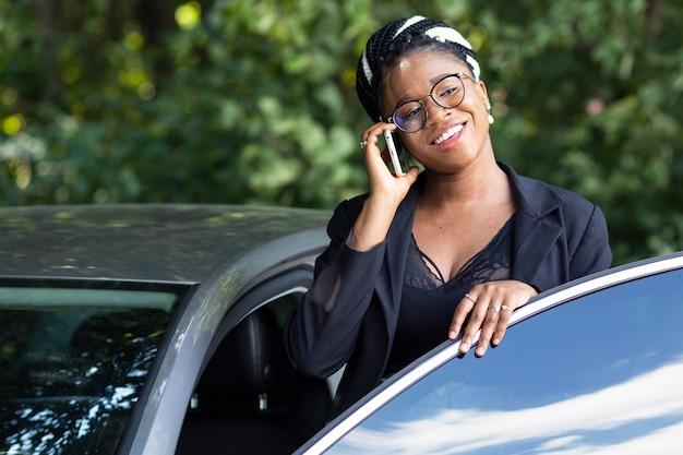Smiley-frau, die auf smartphone spricht, während sie in ihr auto steigt