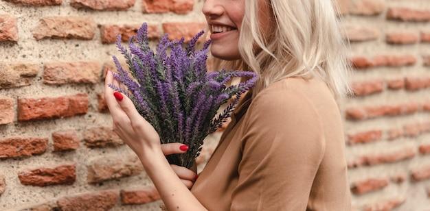 Smiley-frau, die blumenstrauß des lavendels hält