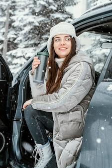 Smiley-frau, die den schnee während einer straßenreise genießt