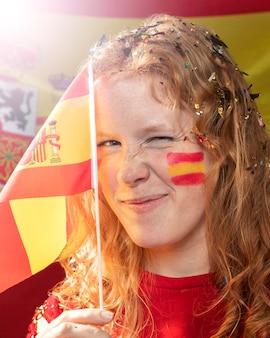 Smiley-frau, die die spanische flagge hält