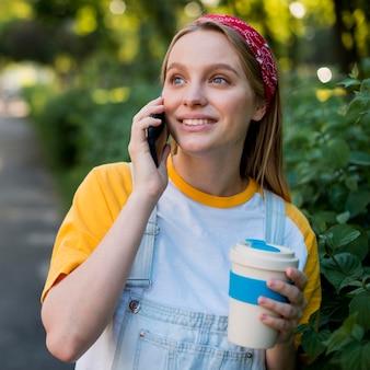 Smiley-frau, die draußen am telefon spricht
