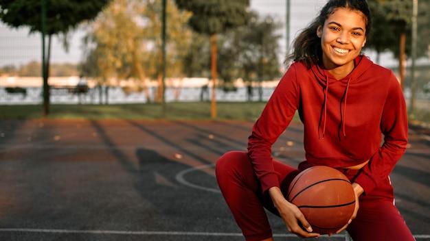 Smiley-frau, die draußen basketball spielt