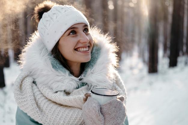 Smiley-frau, die draußen im winter aufwirft