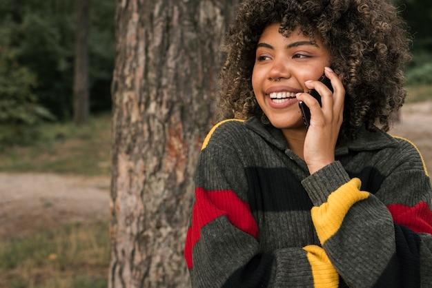Smiley frau, die draußen kampiert und auf smartphone spricht