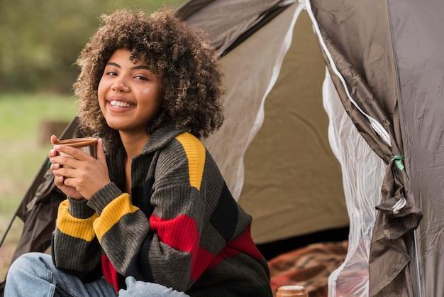 Smiley frau, die draußen mit zelt kampiert