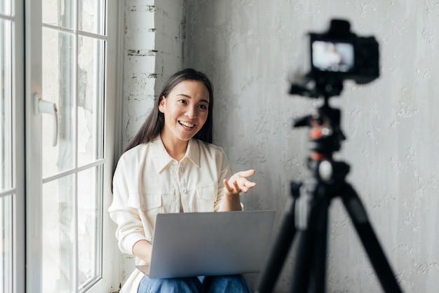 Smiley-frau, die drinnen einen vlog macht