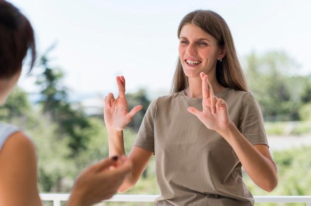Smiley-frau, die durch gebärdensprache im freien kommuniziert